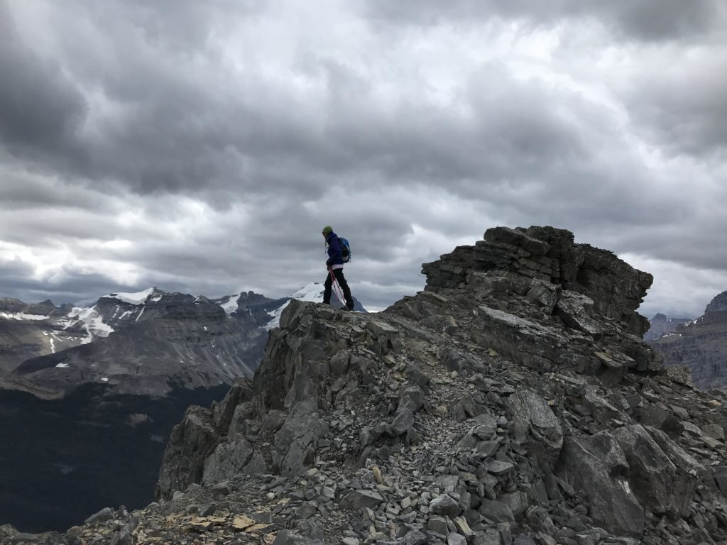 Person standing on a mountain top. Hiking can be relaxing.